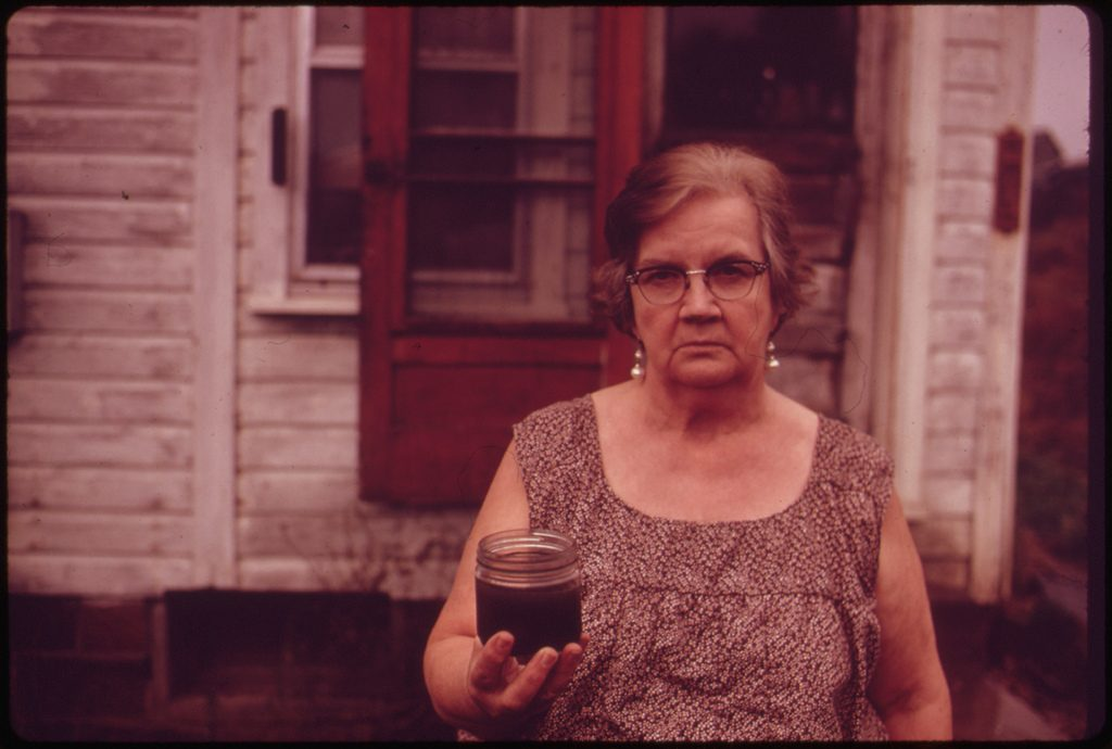Mary Workman holds a Jar of undrinkable water that came from her well in October 1973. This photo is part of the Documerica Project (1971-1977), wherein EPA hired freelance photographers to capture images relating to environmental problems, EPA activities, and everyday life in the 1970s. Photo by Erik Calonius