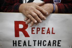 "A Kentucky voter holds a ""repeal healthcare"" sign at a rally for Mitch McConnell (R-KY) in 2014. Photo by Luke Sharrett/Getty Images"