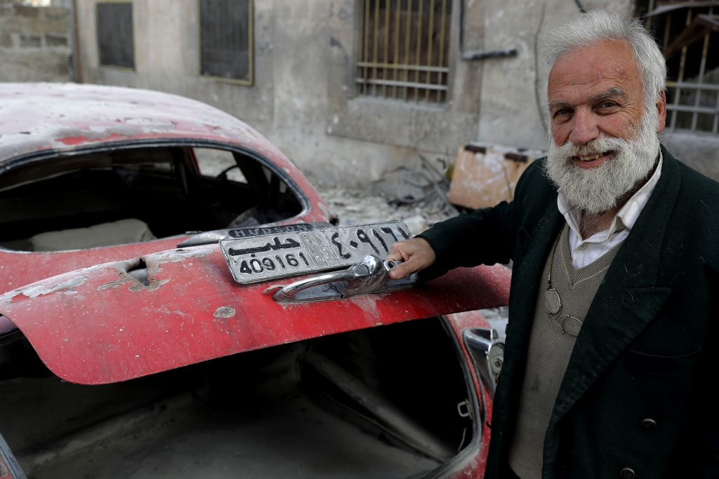 Despite the destruction all around him, Mohammed Mohiedin Anis smiles as he opens the trunk of his 1949 Hudson Commodore. Photo by Joseph Eid/AFP/Getty Images