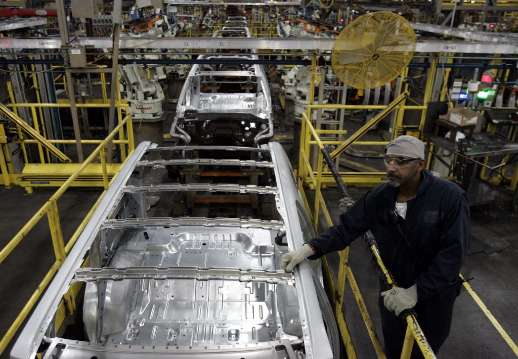 A Ford Motor Company auto worker stands on the assembly line next to 2008 Ford Expedition and Lincoln Navigator SUV frames at the Ford Michigan Truck Plant in Wayne, Michigan August 26, 2008. Ford Motor Co plans to invest $75 million to retool a Michigan truck plant to build cars as part of its effort to boost its product line-up with more fuel-efficient vehicles, the automaker said on Tuesday. REUTERS/Rebecca Cook
