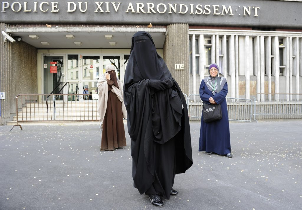 Nayet (C), wearing a Burqa, and Kenza Drider (L), a French Muslim of North African descent, wearing a niqab, are seen after their release from a police station in Paris April 11, 2011. France's ban on full face veils, a first in Europe, went into force today, exposing anyone who wears the Muslim niqab or burqa in public to fines of 150 euros ($216) and lessons in French citizenship. REUTERS/Gonzalo Fuentes (FRANCE - Tags: POLITICS RELIGION CRIME LAW) - RTR2L3TD