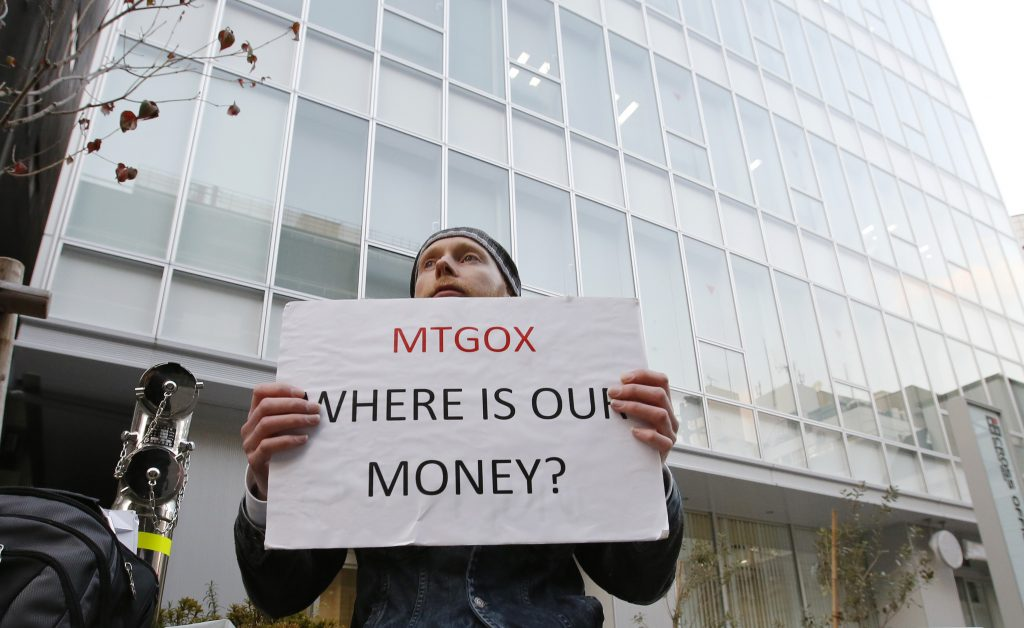 Kolin Burges, a self-styled cryptocurrency trader and former software engineer who came from London, holds a placard to protest against Mt. Gox, in front of the building where the digital marketplace operator is housed in Tokyo February 25, 2014. The website of Mt. Gox appears to be taken down, shortly after six major Bitcoin exchanges released a joint statement distancing themselves from the troubled Tokyo-based bitcoin exchange. Tokyo-based Mt. Gox was a founding member and one of the three elected industry representatives on the board of the Bitcoin Foundation. REUTERS/Toru Hanai (JAPAN - Tags: BUSINESS CIVIL UNREST SCIENCE TECHNOLOGY) - RTR3FP5V
