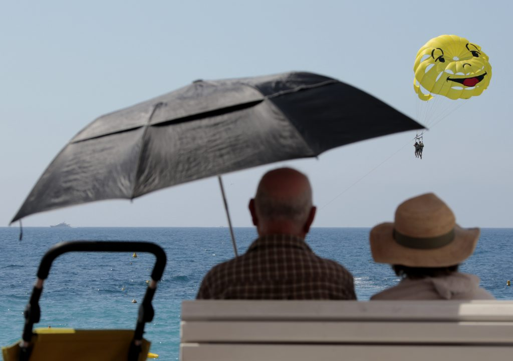 Two elderly people sit on a bench as they look at a parascending during a sunny summer day in Nice, southeastern France, J...