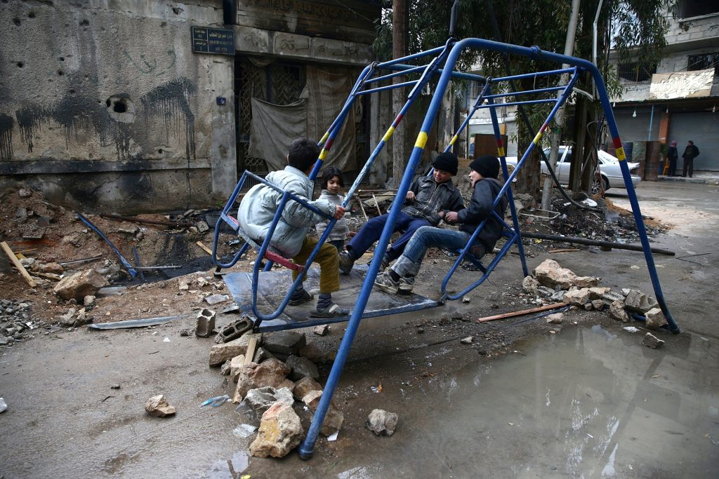 Children play on a swing in the rebel held city of Douma, north-east of Damascus, on March 1. Photo by Bassam Khabieh/Reuters