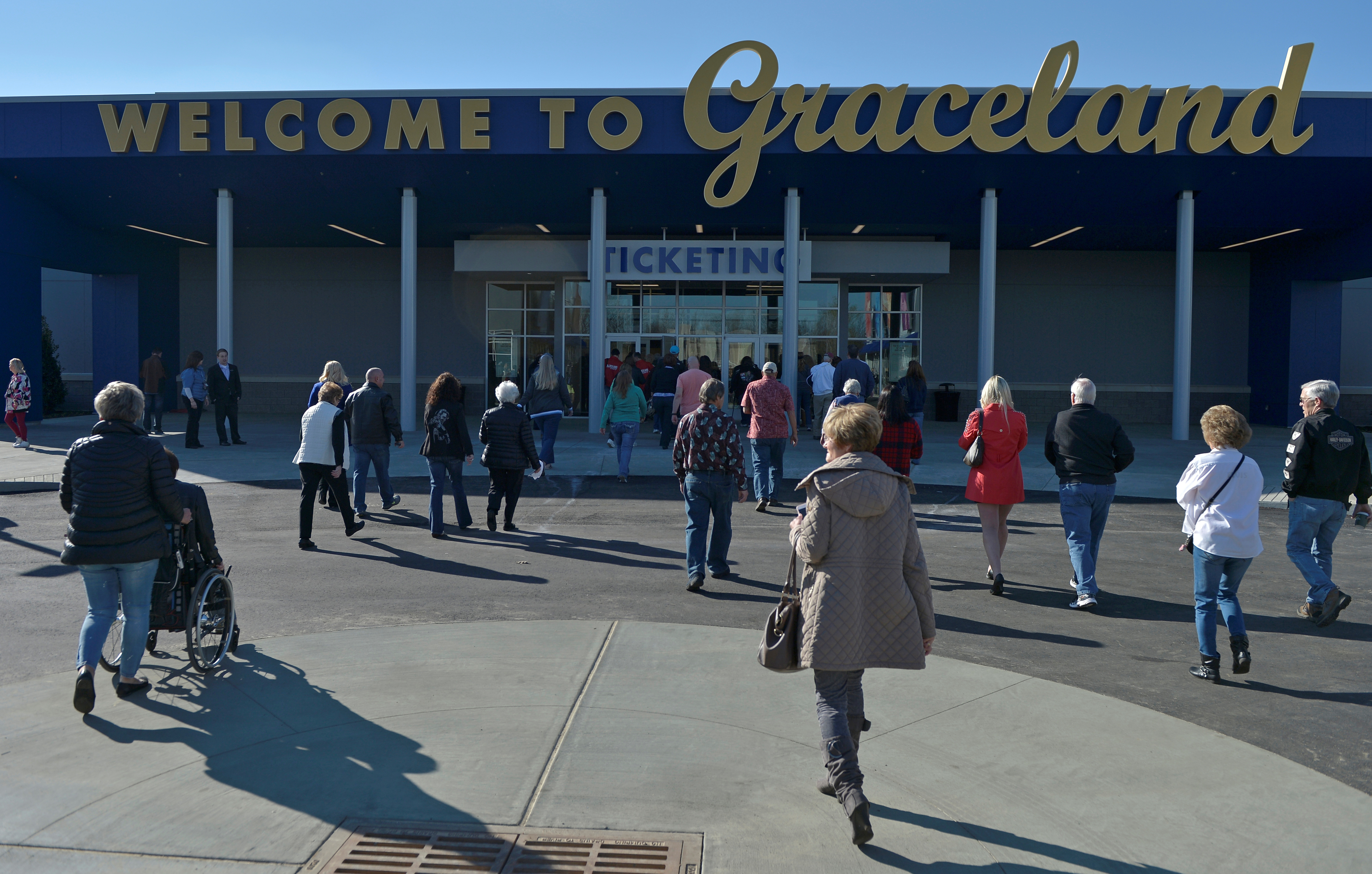 Elvis Presley fans walk in to the ticket office at the grand opening of a complex showcasing the late singer's belongings. Photo by Brandon Dill/Reuters