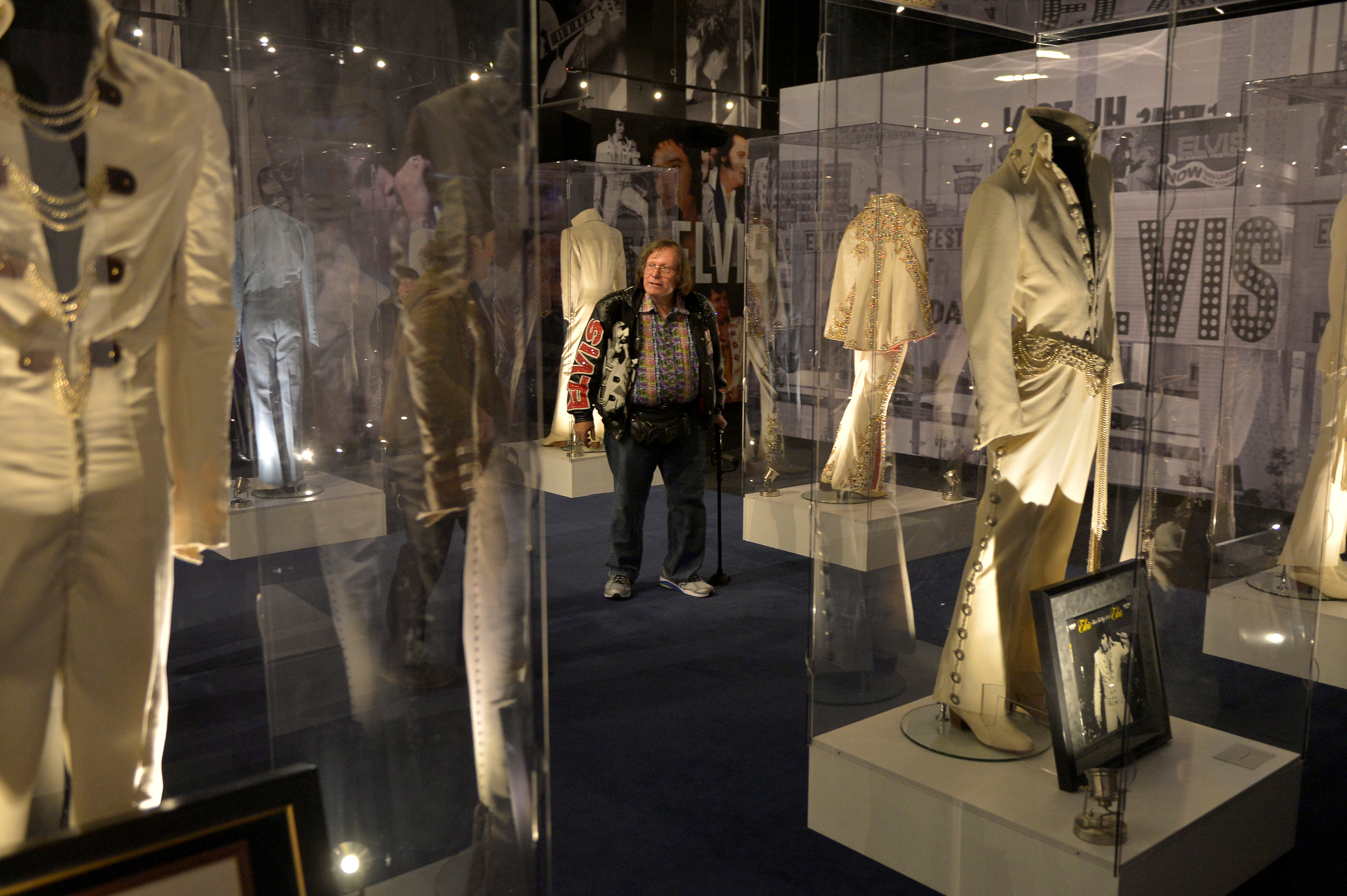 Neil Spencer of Knoxville, Tennessee, walks through a display featuring jumpsuits worn by Elvis Presley. Photo by Brandon Dill/Reuters