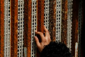 A man, who was deported from the U.S. seven months ago, touches the fingertips of his nephew across a fence separating Mexico and U.S, as photographed from Tijuana
