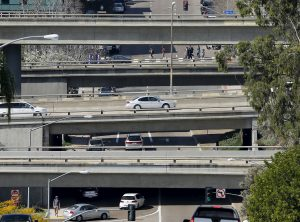 Cars travel on city streets and highway overpasses in San Diego