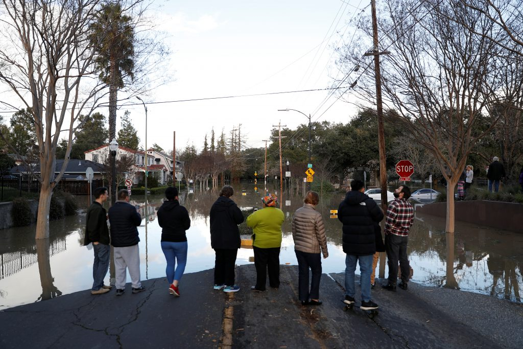 People stand by a flooded street near William Street Park after heavy rains overflowed nearby Coyote Creek in San Jose, California. Photo by Stephen Lam/Reuters
