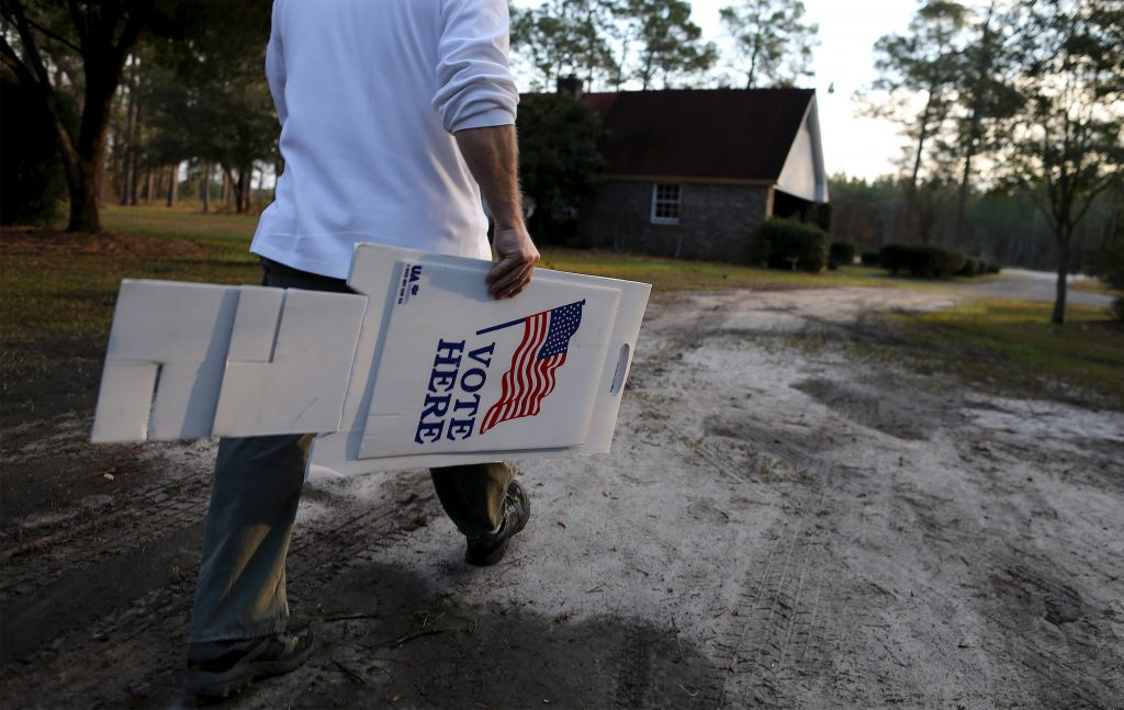 Precinct volunteer David Smith carries a voting sign to the edge of SC Highway 278 outside the Horse Gall precinct in Varnville, South Carolina. The precinct is in the garage of Smith's home in the rural county of Hampton. Photo taken in February 2016. Photo by Randall Hill/Reuters