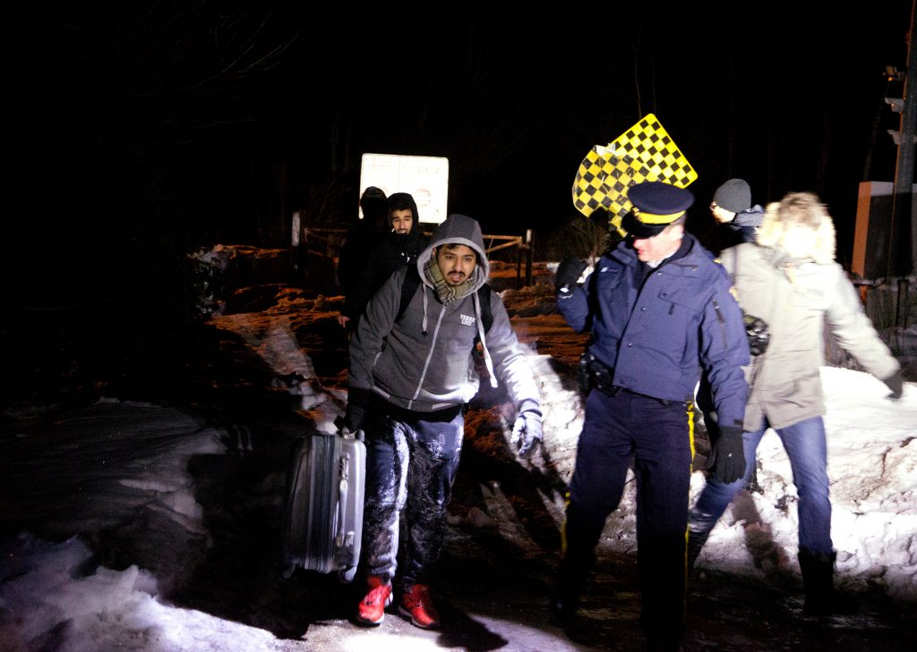 Two men who claimed to be from Yemen cross the border and enter Hemmingford, a village in Quebec, Canada, on March 20. Photo by Christinne Muschi/Reuters