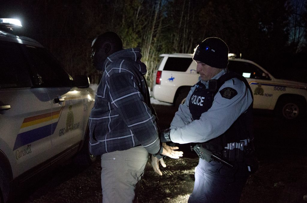 "A man who claimed to be from Sudan and kept saying ""I just want to be safe"" is handcuffed by a Royal Canadian Mounted Police officer after he illegally crossed the U.S.-Canada border on March 20. Photo by Christinne Muschi/Reuters"