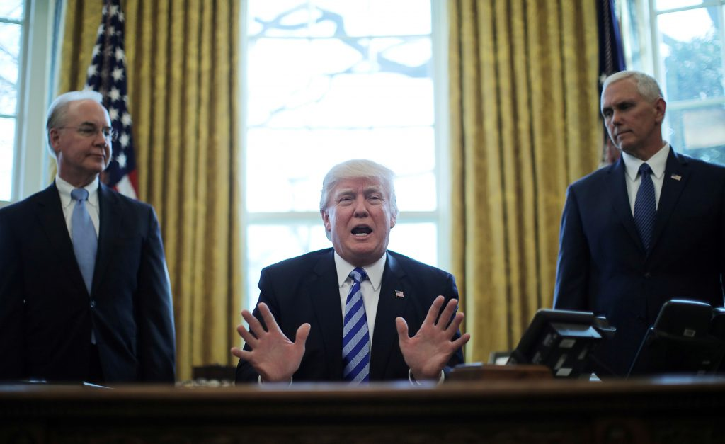 File photo of President Donald Trump sitting between Secretary of Health and Human Services Tom Price (left) and Vice President Mike Pence in the Oval Office of the White House by Carlos Barria/Reuters