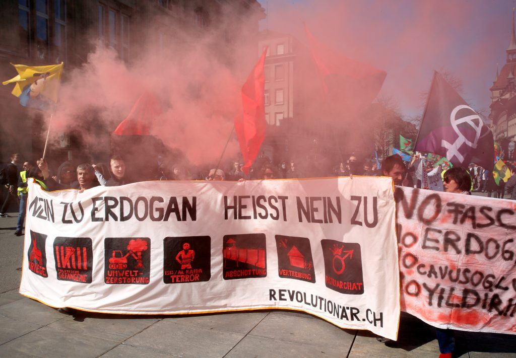 People hold banners and flags during a demonstration against Erdogan dictatorship and in favour of democracy in Turkey in Bern