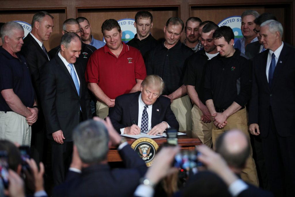 "U.S. President Donald Trump signs an executive order on ""energy independence,"" eliminating Obama-era climate change regulations, during an event at the Environmental Protection Agency (EPA) headquarters in Washington, U.S., March 28, 2017. Photo by Carlos Barria/REUTERS"