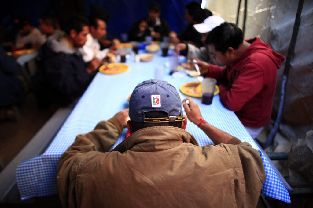 People eat food at an aid center in Nogales, Mexico November 10, 2010. According to the group No More Deaths, a group that aims to end death and suffering along the United States/Mexico border, 253 people have died this year trying to cross the border. Among other duties, the group assists with this aid center, called Aid Center for Deported Migrants (CAMDEP), which is run by Kino Border Initiative. REUTERS/Eric Thayer (MEXICO - Tags: SOCIETY FOOD) - RTXVAPA