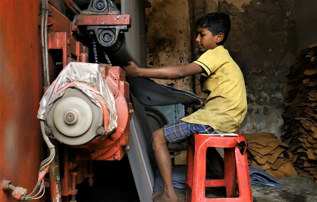 A 10-year-old boy pulls a hide from pressing machine at a tannery in Dhaka, the capital of Bangladesh. Screen shot by Justin Kenny