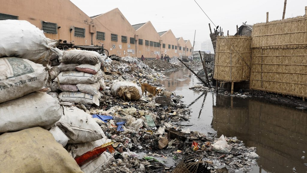 A creek outside a Dhaka tannery has banks covered in garbage and rotting animal hides. Screen shot by Justin Kenny