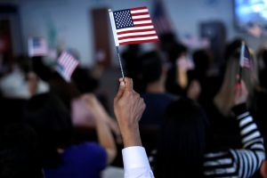 New American citizens wave American flags Mar. 1 after taking the Oath of Allegiance during a naturalization ceremony in Newark, New Jersey. Photo by REUTERS/Mike Segar.