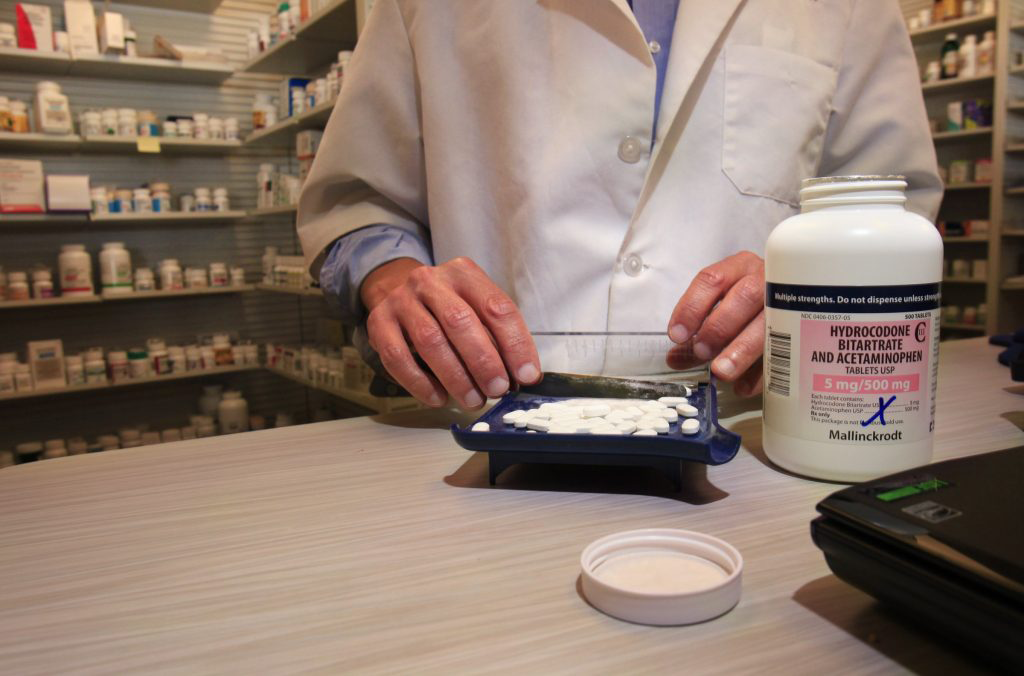 A pharmacist counts out pills of Vicodin at a pharmacy. Vicodin is one of the drugs a lawsuit claims was over-distributed to NFL players. Photo by Gregory Rec/Portland Press Herald via Getty Images.