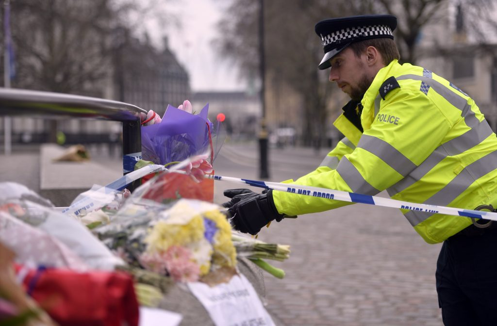A police officer reaches out to floral tributes in Westminster the day after the attack in London. Photo by REUTERS/Hannah McKay - RTX32CM8