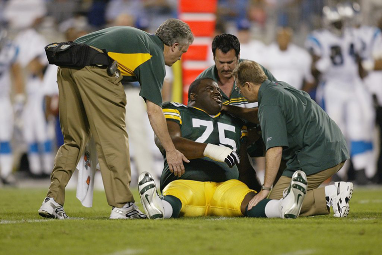 Head trainer Pepper Burruss (L) and two other medical staff of the Green Bay Packer assist injured Packer defensive tackle Grady Jackson #75 during a 2004 game against the Carolina Panthers. Burruss was one fo the trainers and coaches whose memos were obtained in a court filing reported by the Washington Post. Photo by Streeter Lecka/Getty Images.