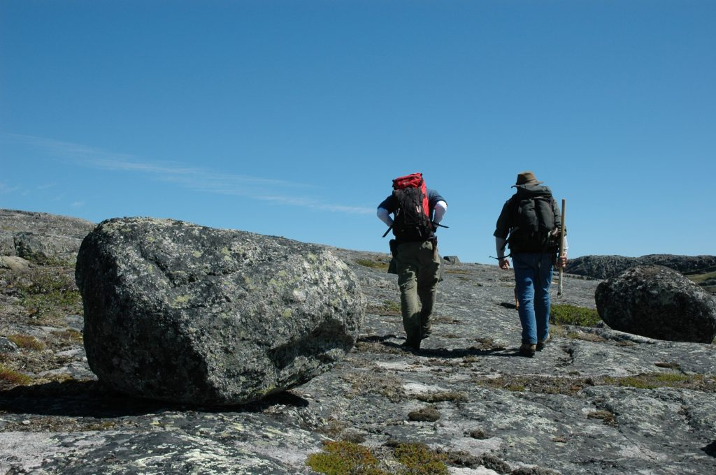 Researchers Jonathan O'Neil and Don Francis returning to camp with backpacks full of rock samples. Photo by Alexandre Jean