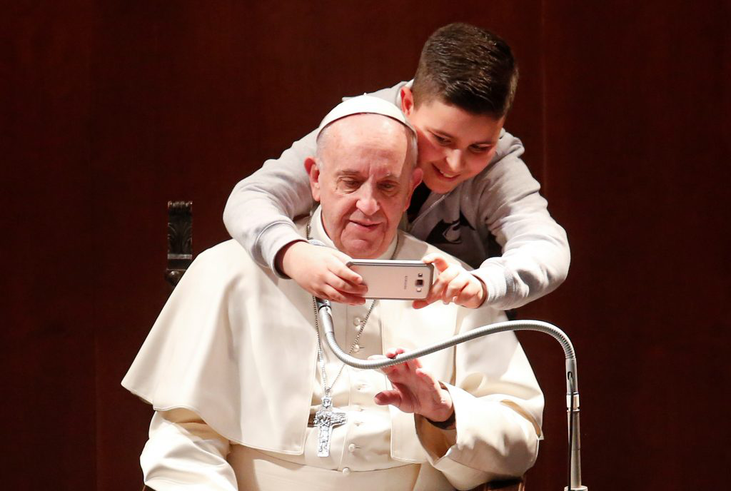 A boy takes selfies with Pope Francis during a visit  Feb. 19 at the parish of St. Mary Josefa of the Heart of Jesus in Rome. Photo by REUTERS/Remo Casilli.