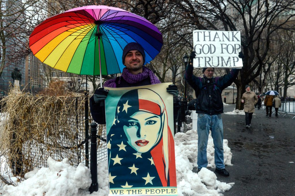 A man protesting President Donald Trump's immigration policies and supporting refugees stands in front of a Trump supporter Feb. 17 in New York City. Photo by REUTERS/Stephanie Keith.