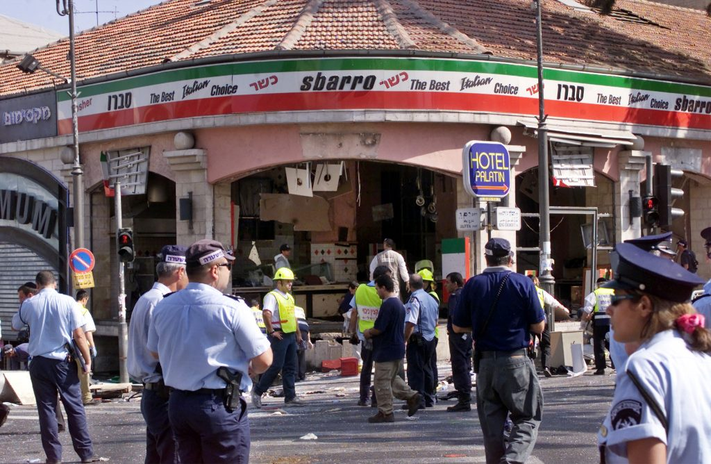 A gaping hole is left in the shop front of the Sbarro pizzeria after a suicide bombing that killed at least 18 people and wounded more than 80 others in Jerusalem August 9, 2001. Photo by Reuters.