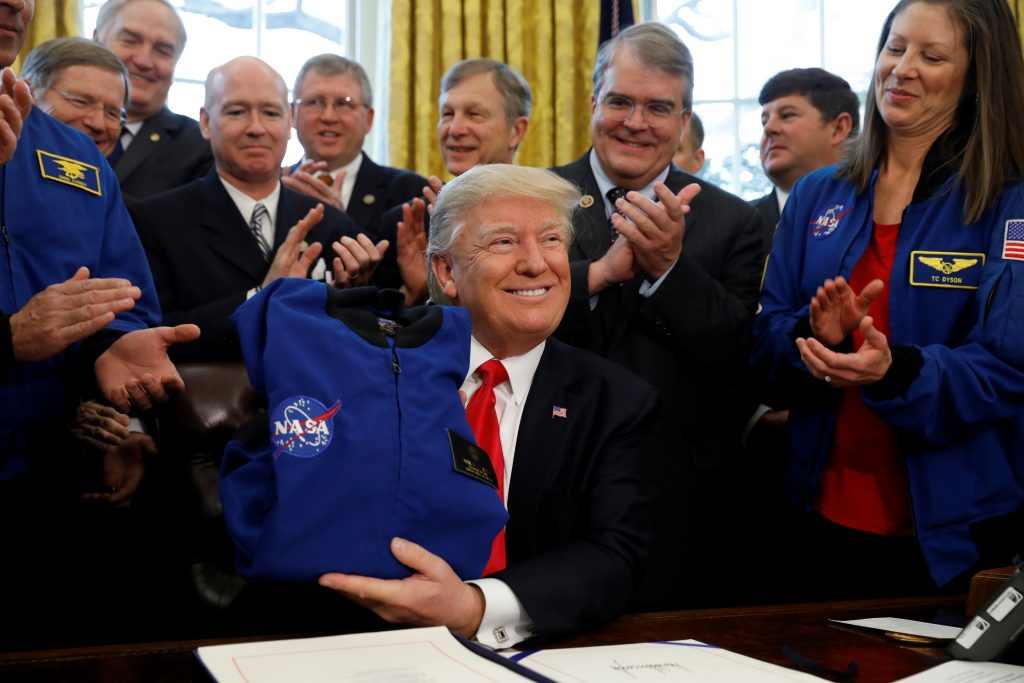 U.S. President Donald Trump receives a NASA jacket during a signing ceremony for S442, the NASA transition authorization act, in the Oval Office of the White House in Washington, U.S., March 21, 2017. Photo by Kevin Lamarque/REUTERS