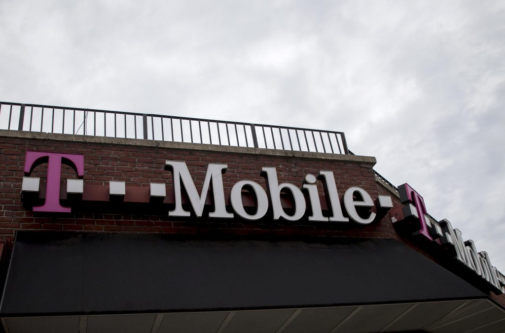 People pass by a T-Mobile store in the Brooklyn borough of New York. Photo by REUTERS/Brendan McDermid.