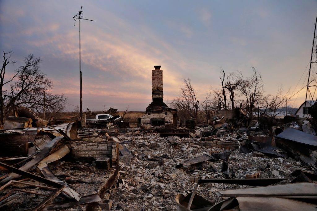 A chimney is all that stands in the footprint of a home destroyed by wildfires near Laverne, Oklahoma.