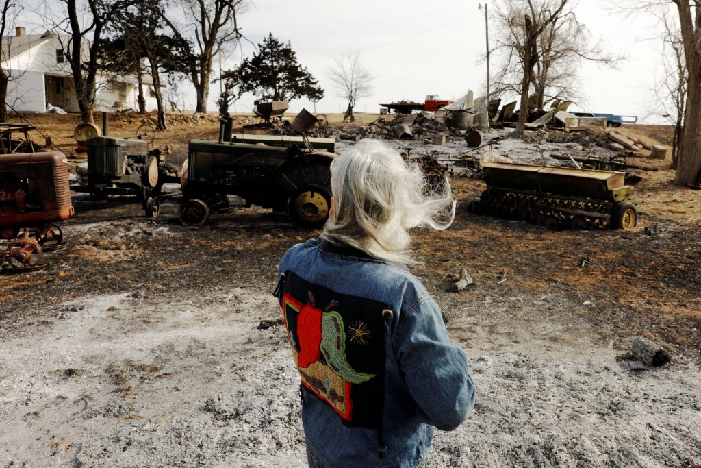 Kay Rottmayer, 65, looks at farm equipment that was destroyed by wildfires near Knowles, Oklahoma. Photo by Lucas Jackson/Reuters