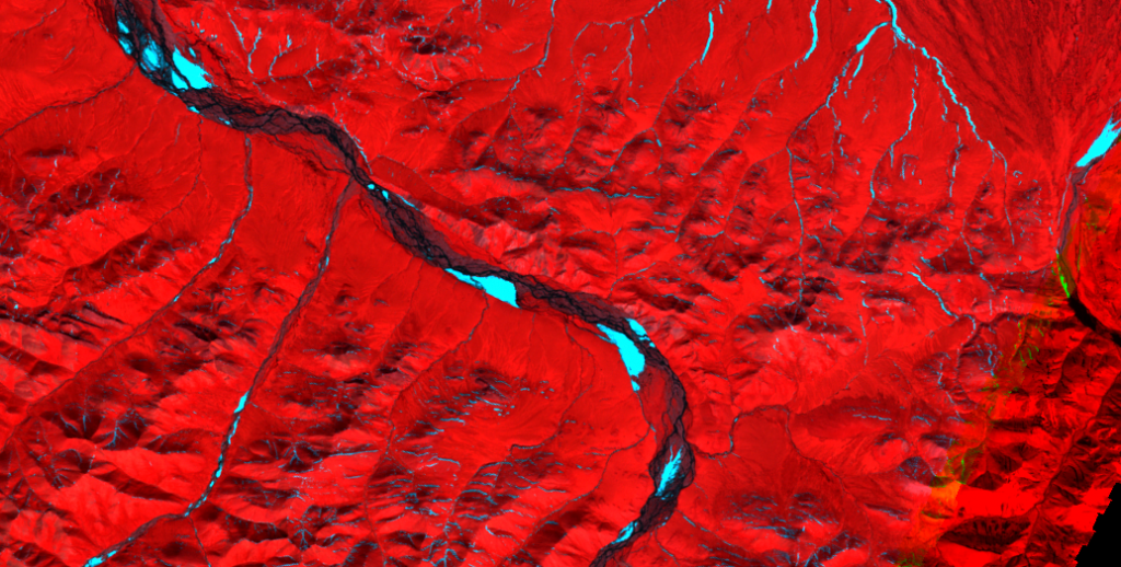 Kongakut River, ephemeral icings, June 16, 2001. Aufeis and unmelted snow bands are bright blue. Image taken by Landsat 7