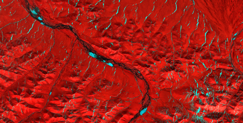 Kongakut River, ephemeral icings, June 18, 2013. Aufeis and unmelted snow bands are bright blue. Image taken by Landsat 8