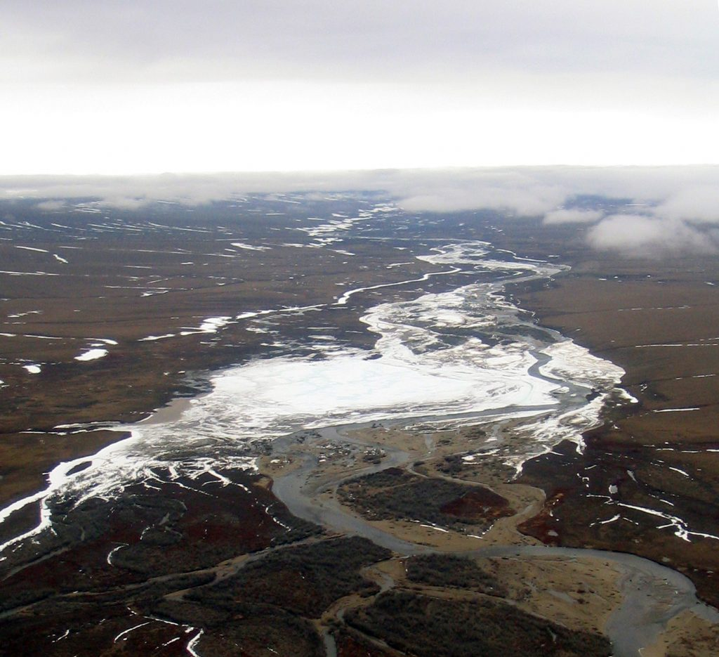 The aerial image (Kuparuk_Aufeis) is taken from a helicopter of a larger river icing on the Kuparuk River just north of the University of Alaska Fairbanks managed Toolik Field Station and the National Science Foundation supported Arctic Long Term Ecological Research site on the North Slope of Alaska. Photo by Jay Zarnetske