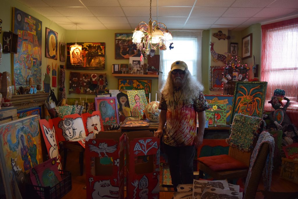 Brian Dowdall in his living room in his Baltimore home, standing with recent animal spirit paintings, and other outsider art.