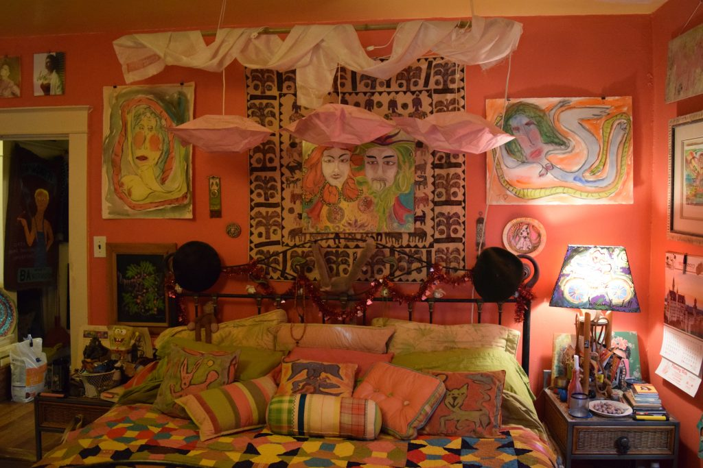 Brian Dowdall and Alison Spiesman's bedroom at the Baltimore house, where goddess paintings are hung over the bed. Photo by Elizabeth Flock