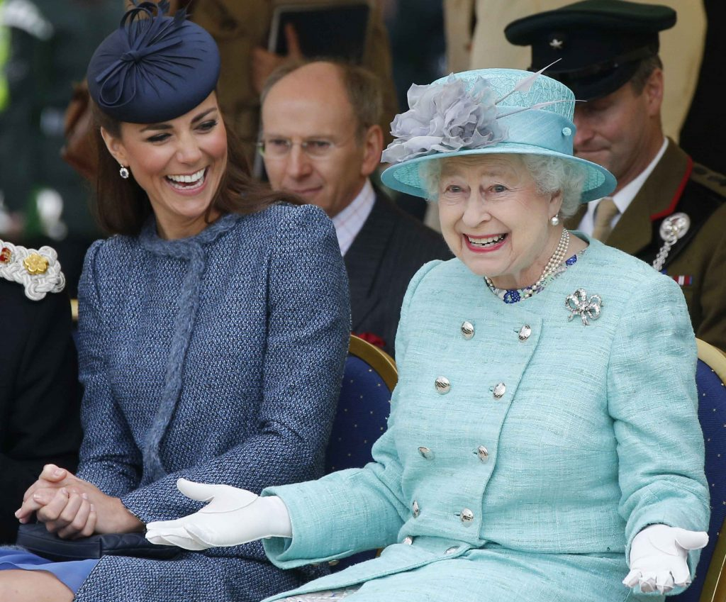 Catherine, duchess of Cambridge (left), and Queen Elizabeth II share a laugh at a children's sports event in Nottingham, England, on June 13, 2012. Photo by Phil Noble - WPA Pool/Getty Images