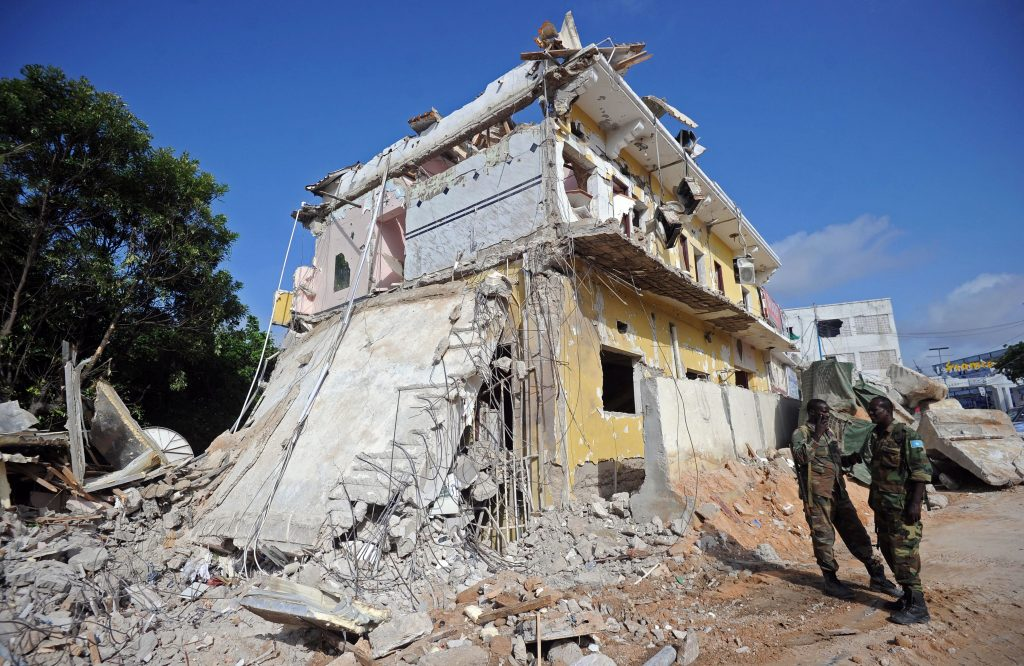 Somali soldiers stand guard on June 26, 2016 at the scene of the terror attack on a hotel in Mogadishu that killed at least 11 people the previous day and was claimed by al-Shabab militants. Photo by Mohamed Abdiwahab/AFP/Getty Images