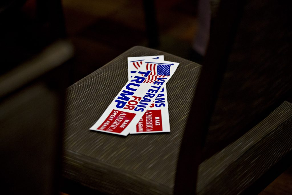 """""""Veterans for Trump"""" bumper stickers sit on a chair before a 2016 c…"""