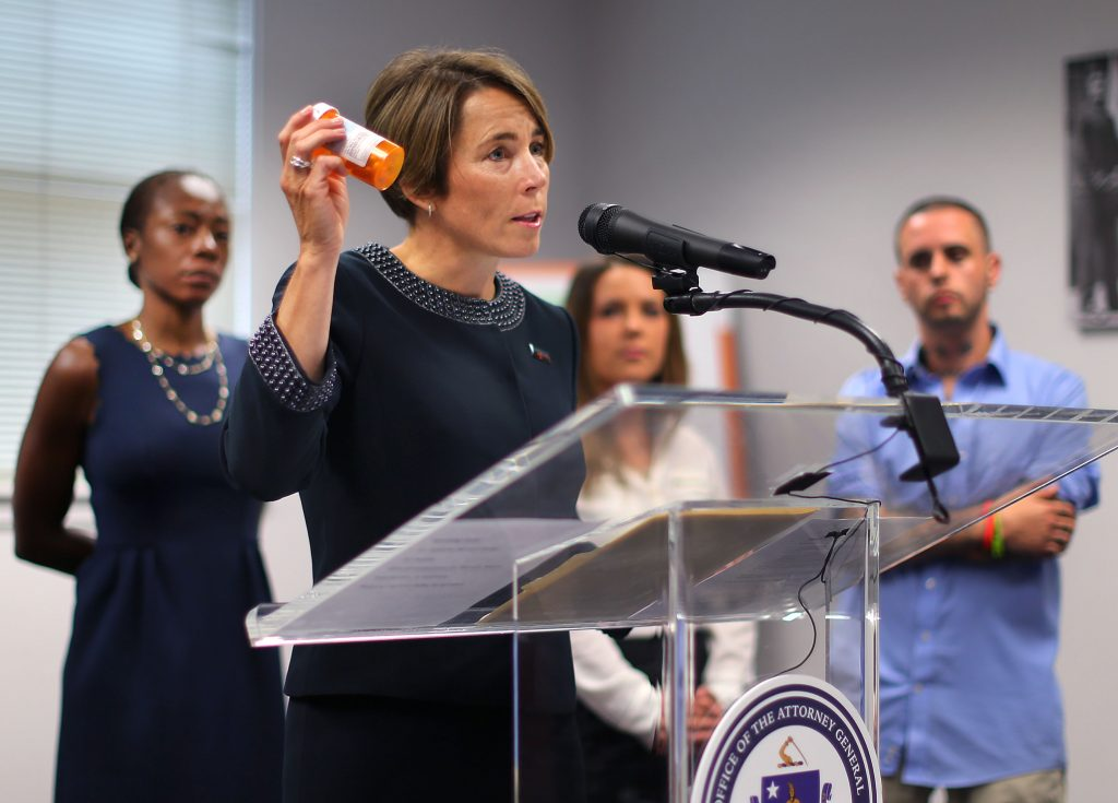 Attorney General Maura Healey holds a CVS prescription bottle as she announced in a first-in-the-nation settlement -- that CVS Pharmacy will strengthen its policies and procedures around the dispensing of opioids -- at The Dimock Center on Sept. 1, 2016. Photo by John Tlumacki/The Boston Globe via Getty Images