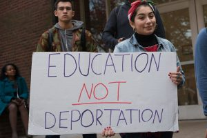 "Rutgers University student holds a sign that reads ""Education not deportation."""
