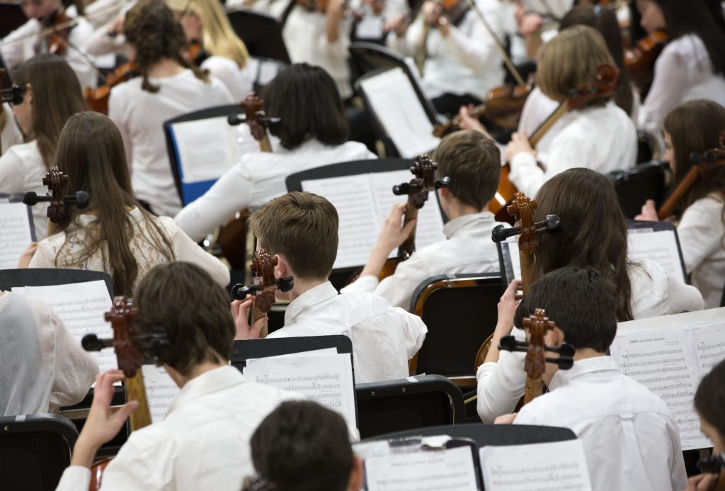 View of the back of the cello section in a youth orchestra.