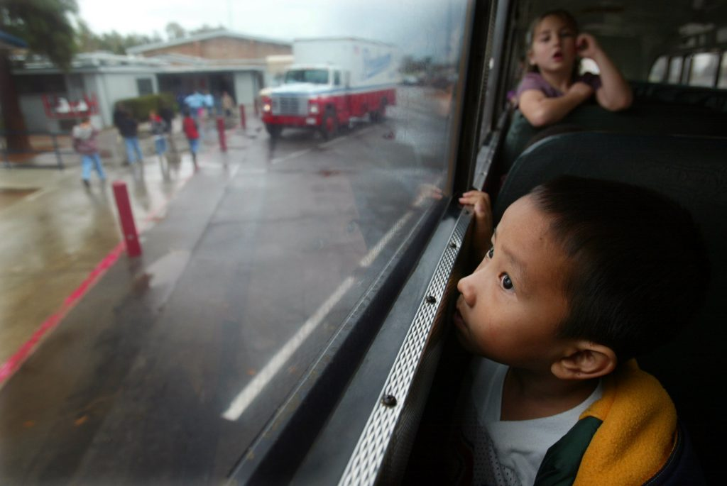 Pao Ge Vang, age 5 looks out of the school bus on his way home after his second day in kindergarten 4 in Fresno, California, after arriving in U.S. from Thailand with his family as part of a U.S. government resettlement program. Photo by Paula Bronstein/Getty Images