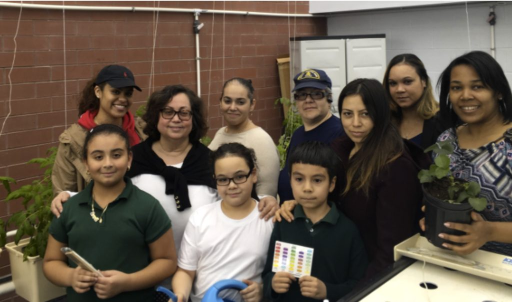 Yvonne Lassalle, science teacher (left with glasses) with staff, parents, current and former students of the Cypress Hills Community School in the Cypress Hills Greenhouse.