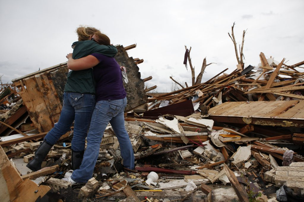 Volunteer Madison Welch (L) consoles Amy Jennings, who found a picture of her father in the rubble of her mother's home after a tornado struck Joplin, Missouri May 25, 2011. Tornadoes have killed nearly 850 people in the U.S. since 2010. Photo by Eric Thayer/Reuters