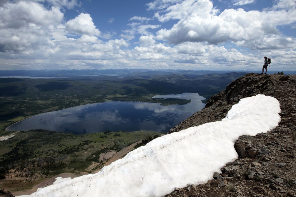 Hiker stands on top of Mount Sheridan, overlooking Heart Lake in the Red Mountains of Yellowstone National Park, Wyoming
