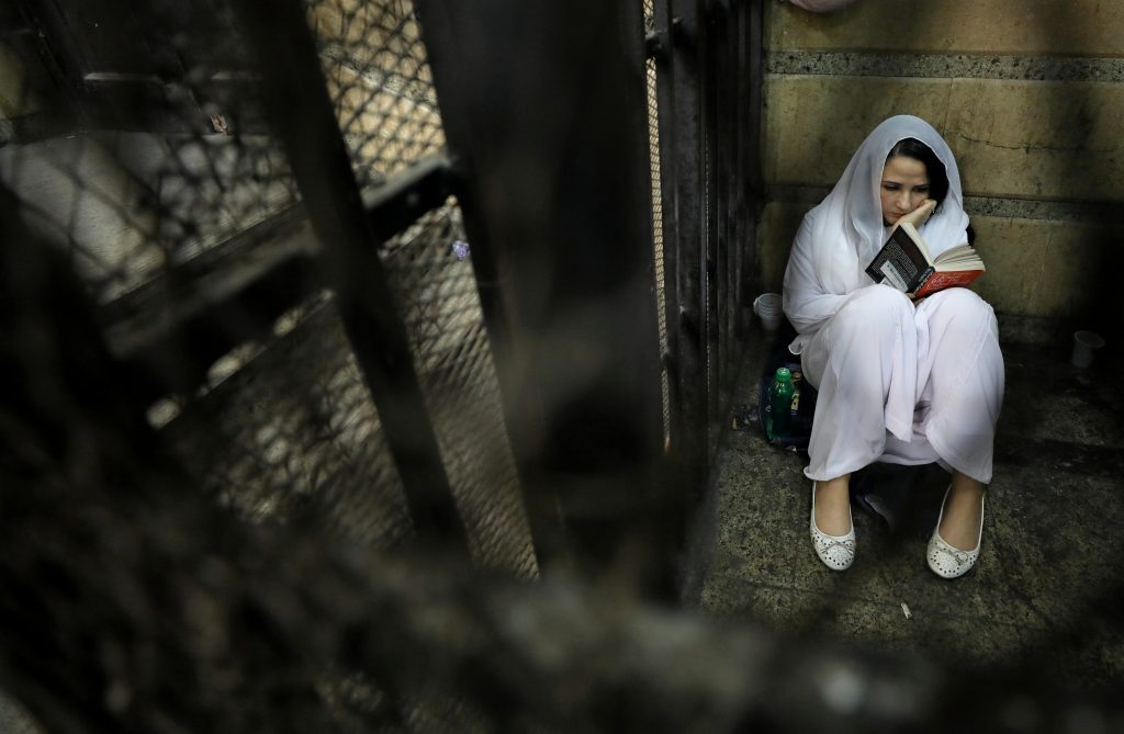 Aya Hijazi, founder of Belady, an NGO that promotes a better life for street children, sits reading a book inside a holding cell in Cairo, Egypt. Picture taken March 23, 2017, about a month before she was cleared of child abuse and human trafficking charges. Photo by Mohamed Abd El Ghany/Reuters